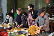 """Aladdin Charni cooking with volunteers in the kitchen. Cofounder of Freegan Pony Gilia Bataille is behind.<br /><br />The Freegan Pony is an alternative restaurant housed in a squat. It was founded in 2015 by Aladdin Charni with three other collaborators. The restaurant specialises in cheap vegetarian cuisine, serving meals which guests reserve a place through a Facebook group, paying €2 a meal. The restaurant meals contain unsold and donated food, collected from wholesellers at the Paris Rungis vegetable market. The Freegan Pony is located at the Porte de la Vilette on the outskirts of Paris, at the entrance to the peripherique outer circle motorway.<br /><br />Freegans are people who employ alternative strategies for living based on limited participation in the conventional economy and minimal consumption of resources. Freeganism is the practice of reclaiming and eating food that has been discarded. People who attempt to live an ethical lifestyle by reusing trash and rubbish thrown away by others.<br /><br />Freeganism is an ill-defined activity and is a subset of the larger anti-capitalist and environmental protest movements. It embraces alternative, anti-consumerist lifestyles. Freegan practices also include co-operative living, squatting and """"freecyling"""", or matching things that people want to get rid of with things other people need"""