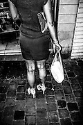 June 2015. Brussels. A woman holds a plastic bag in front of a shop on the street.
