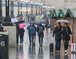 London, January 02 2018. People make their way along the bank of the River Thames near Tower Bridge as rain descends on the capital . © SWNS