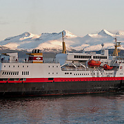 Three weeks aboard the Kong Harald. Hurtigruten, the Coastal Express. The Narvik leaving Molde Harbour, with mountains under snow.