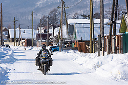 Cold weather adventure motorcyclist Alessandro Ciceri, better known as Wizz (@wizz_inwiaggio), riding through the village of Maksimiha in Siberia after he rode 6,200 mile (10,000 km) from his home in Italy in the middle of winter and after racing in the Baikal Mile Ice Speed Festival. Maksimiha, Siberia, Russia. Monday, March 2, 2020. Photography ©2020 Michael Lichter.
