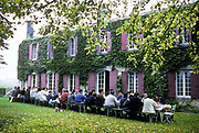 "Seasonal grape pickers having lunch during the annual ""vendage"" at the famed Chateau Margaux wine estate, Bordeaux, France"