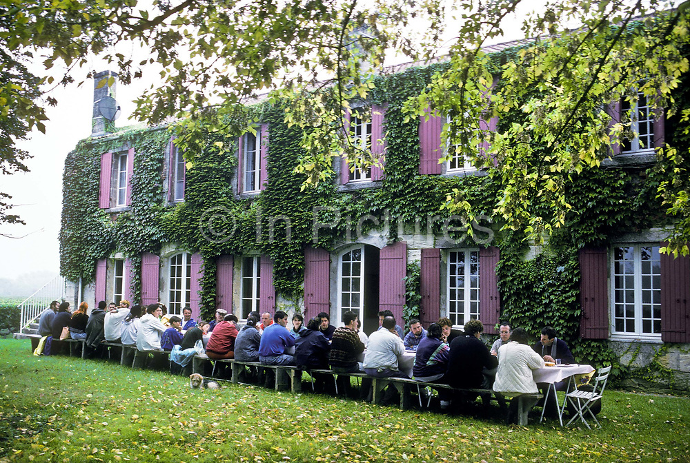 """Seasonal grape pickers having lunch during the annual """"vendage"""" at the famed Chateau Margaux wine estate, Bordeaux, France"""