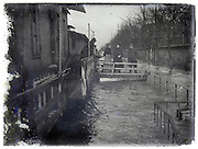 people on the bridge of their houseboat during flooding of the Seine River, Paris January 1910