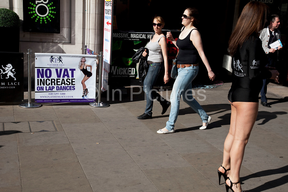 Woman giving out leaflets to passers by outside Platinum Lace, a high end Lap dancing club in the West End of London. The woman (possibly a lap dancer) wearing short shorts revealing her legs. Amusingly the sign outside the club reads 'No VAT increase on lap dances'. Surely an incentive in these economically difficult times.