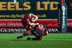 Scarlets' Ken Owens is tackled by Dragons' Thomas Davies<br /> <br /> Photographer Craig Thomas/Replay Images<br /> <br /> Guinness PRO14 Round 13 - Scarlets v Dragons - Friday 5th January 2018 - Parc Y Scarlets - Llanelli<br /> <br /> World Copyright © Replay Images . All rights reserved. info@replayimages.co.uk - http://replayimages.co.uk