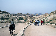 Swan Hellenic tour group tourists walking to archaeological site at Petra, Jordan in 1998