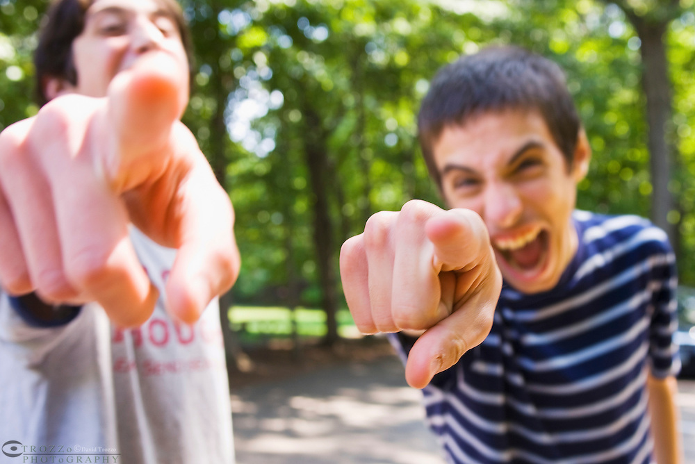 Teen aged boys point and laugh and tease offering unwanted criticism.