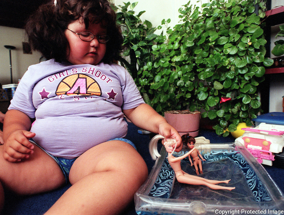 Four year-old, Anamarie Regino, plays with her barbie dolls in her Albuquerque home. Anamarie, at age 4, is already on a diet and exercise program but no-one knows why her weight has soared so high.