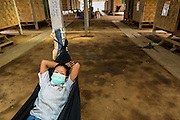 03 MARCH 2104 - MAE KASA, TAK, THAILAND: A TB patient relaxes in a hammock at the Sanatorium Center for Border Communities in Mae Kasa, about 30 minutes north of Mae Sot, Thailand. The Sanatorium provides treatment and housing for people with tuberculosis in an isolated setting for about 68 patients, all Burmese. The clinic is operated by the Shoklo Malaria Research Unit and works with several other NGOs that assist Burmese people in Thailand. Reforms in Myanmar have alllowed NGOs to operate in Myanmar, as a result many NGOs are shifting resources to operations in Myanmar, leaving Burmese migrants and refugees in Thailand vulnerable. Funding cuts could jeopardize programs at the clinic. TB is a serious health challenge in Burma, which has one of the highest rates of TB in the world. The TB rate in Thailand is ¼ to ⅕ the rate in Burma.        PHOTO BY JACK KURTZ