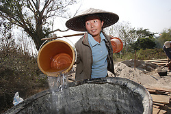 Nom 33 years old has 4 children and she has carried water up from the river into a large barrel, it will be used for mixing concrete. Village Had Mad, Pak Ou district Luang Prabang Province. Lao PDR