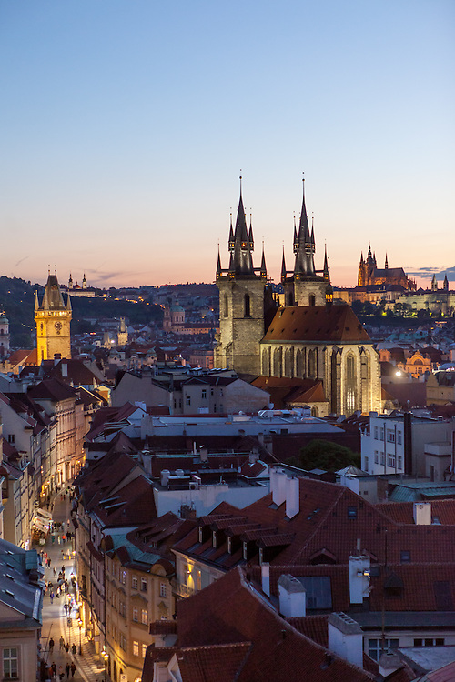 "View to the Prague cityscape and ""Celetna street"" and the towers of Tyn Church located at Old Town Square. On the right Prague Castle and St. Vitus Cathedral during sundown."