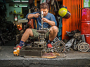 14 AUGUST 2014 - BANGKOK, THAILAND:     A man works on a car transmission in front of a shop in the Talat Noi section of Bangkok. Talat Noi is a small part of Chinatown that dates back to the Ayutthaya period. It is a melting pot of various cultures and was originally settled by Portuguese,  Vietnamese, Hokkien, Teochew and Hakka Chinese. Now it is mostly small mechanical shops and used car parts.   PHOTO BY JACK KURTZ