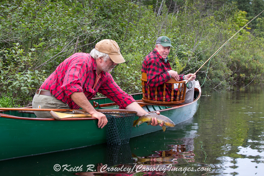 Brule River Guide Damian Wilmot prepares to release a nice brown trout caught by angler Matson Holbrook while fishing the Upper Brule near Lake Nebagamon, Wisconsin, from  a 1895 Lucius guide canoe restored by Wilmot.