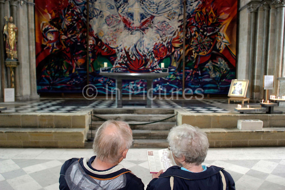 Two tourists look at The Benker Schirmer Tapestry, the retroquire, Chichester Cathedral, West Sussex. in Chichester Cathederal