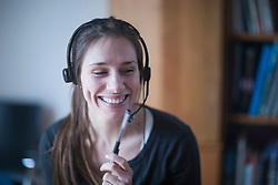 Young woman smiling and talking on headset, Freiburg im Breisgau, Baden-Wuerttemberg, Germany