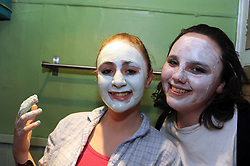 Teenage girls put facemask beauty treatments on at a sleepover