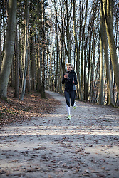 Fit woman with smart phone and headphones jogging in forest