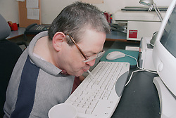 Man with Cerebral Palsy using tool to type on computer keyboard,