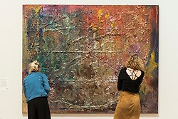 """© Licensed to London News Pictures. 30/05/2019. LONDON, UK. Staff members view """"Spreadout Ron Kitaj"""", 1984-6, by Frank Bowling at a preview of works by artist Frank Bowling (born in Guyana in 1934).  The retrospective exhibition spans his six-decade career and takes place 31 May to 26 August 2019 at Tate Britain.  Photo credit: Stephen Chung/LNP"""