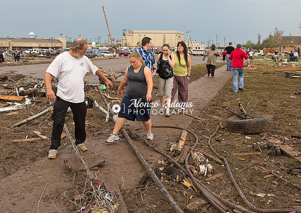 People step over down power lines along Telephone Road just south of 4th Street in Moore, Okla. following a deadly EF5 tornado on May 20, 2013.  (Photo copyright © 2013 Alonzo J. Adams)