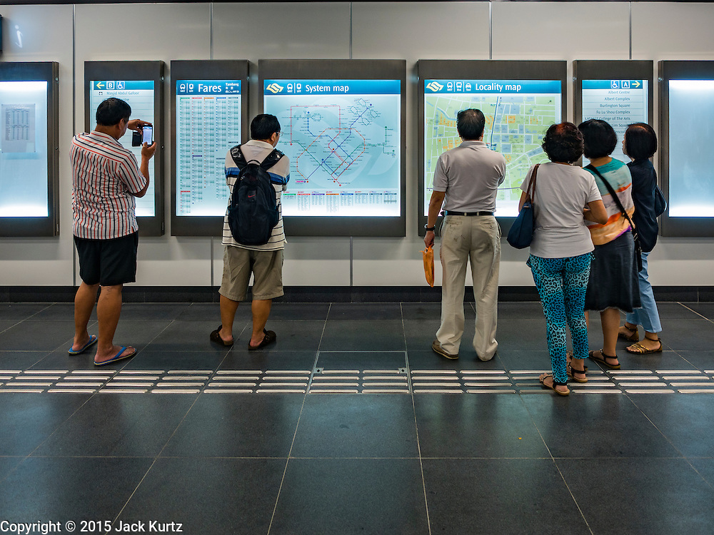 """27 DECEMBER 2015 - SINGAPORE, SINGAPORE:  People look at maps in the Rochor subway station in the Little India section of Singapore on the first day the station was open. Singapore opened the extension of the Downtown Line on its subway system Sunday. The extension is a part of Singapore's plans to make the city-state a """"car lite"""" metropolis with plans to double the current subway to more than 360 kilometers of track by 2030. The government plans to have 80% of homes within a 10 minute walk of a subway station.   PHOTO BY JACK KURTZ"""