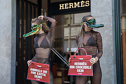 Two PETA supporters wearing Venetian crocodile masks pose outside the Hermès store in New Bond Street in protest against the luxury fashion house's use of exotic skins on 8th September 2021 in London, United Kingdom. PETA's campaign was launched following the release of video footage by The Kindness Project showing crocodiles being mutilated, electrocuted, stabbed and shot on farms in Australia with ties to Hermès and PETA are calling on the fashion brand to cease using exotic skins for their products.