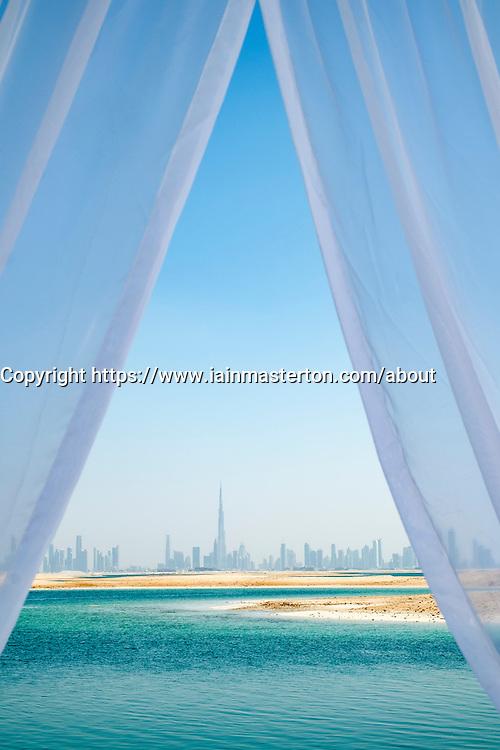 Skyline of Dubai from The Island Lebanon beach resort on a man made island, part of The World off Dubai coast in  United Arab Emirates