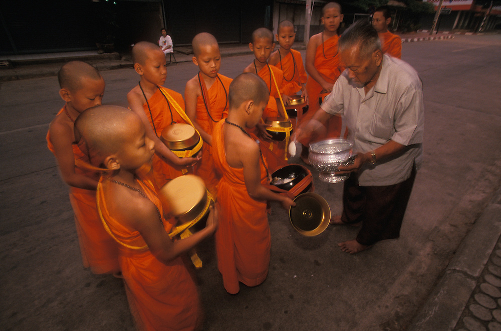 A man gives rice to novice monks who walk the streets with their food bowls early in the morning, Mae Hong Son, Thailand.