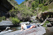 Woman sunbathing on rock by rapids in the channel of the River Rio Poqueira gorge valley, High Alpujarras, Sierra Nevada, Granada Province, Spain