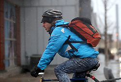April 13, 2018 - Minneapolis, MN, USA - United States - Sleet falls on cyclist biking down Washington Ave. in downtown with snow storm expected to dump up to a foot of snow looming Friday, April 13, 2018, in Minneapolis, MN.]....DAVID JOLES • david.joles@startribune.com.... Minnesota braces for winter storm expected to hit the Twin Cities Friday afternoon. (Credit Image: © David Joles/Minneapolis Star Tribune via ZUMA Wire)