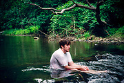 Depressed man sitting in a river.
