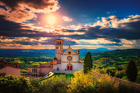 """The sun sets over the Papal Basilica of St. Francis of Assisi""...<br />
