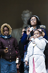Family watching inauguration of Barack Obama from front steps of Lincoln Memorial with Lincoln statute in background, Washington D.C., USA.