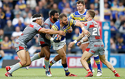 Leeds Rhinos' Adam Cuthbertson is tackled by (left-right) Catalans Dragons' David Mead, Samisoni Langi and Lewis Tierney, during the Betfred Super League match at Emerald Headingley Stadium, Leeds.