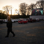 Although a few choose to briefly exit their cars, staff at Retro Drive-In Movies stay vigilant making sure people maintain a safe social distance. Dublin, Ireland - March 24, 2020.