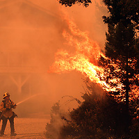 Cal Fire's David Widaman trains his hose on a flames as he and his Cal Fire crew defend a home in the Pineridge neighborhood in Bonny Doon, California as the CZU August Lightning Complex ravages the Santa Cruz Mountains on August 19, 2020.