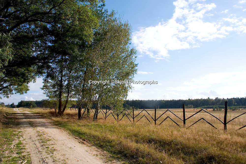 Dirt road along fence dividing farmer's fields with the national forest in the background in Poland.  Zawady  Central Poland