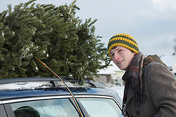 Young man strapping the Christmas tree on the roof of his car, Bavaria, Germany