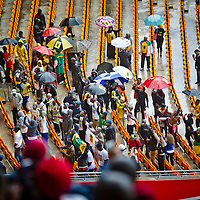JOHANNESBURG, SOUTH AFRICA - 10 DECEMBER 2013, thousands of people gathered to pay their last respects to the late former South African President, Nelson Mandela, during the official National Memorial service held at the FNB stadium in Soweto, outside Johannesburg. Mourners sing in the rain during the celebration.<br /> Photo by ImageSA