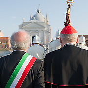 VENICE, ITALY - JULY 16: The Patriarch of Venice Monsignor Angelo Scola (R) and the Mayor of Venice (L) walk on 330mt pontton bridge towards the Redentore church on July 16, 2011 in Venice, Italy. Redentore is one of the most loved celebrations by Venetians which is a remembrance of the end of the 1577 plague. Highlights of the celebration include the pontoon bridge extending across the Giudecca Canal, gatherings on boats in the St Mark's basin and spectacular fireworks on display.