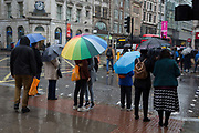 A couple kiss beneath an umbrella as Storm Georgina swept across parts of Britain and in central London, lunchtime office workers were caught out by torrential rain and high winds, on 24th January 2018, in London, England. Pedestrians resorted to leaping across deep puddles at the junction of New Oxford Street and Kingsway at Holborn, the result of overflowing drains.