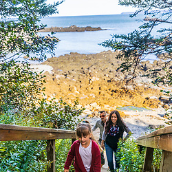 A young girl and her family climb stairs up from a rocky beach at Quoddy Head State Park in Lubec, Maine.