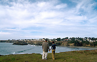 Young couple standing on headland cliff overlooking Mendocino California
