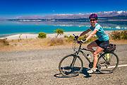 Cyclist riding along the Lake Pukaki under the Southern Alps, Canterbury, South Island, New Zealand