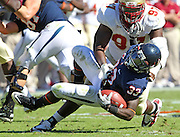 Oct 2, 2010; Charlottesville, VA, USA; Virginia Cavaliers running back Perry Jones (33) is tackled by Florida State Seminoles defensive tackle Demonte McAllister (97) during the 2nd half of the game at Scott Stadium. Florida State won 34-14.  Photo/The Daily Progress/Andrew Shurtleff