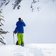 Tyler Hatcher skins up for another run in the Cascade backcountry during a winter storm and shoots an instagram photograph of the light.