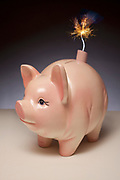 Piggy bank with stick of dynamite and burning fuse for a tail