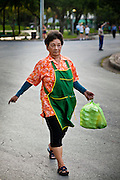 07 JULY 2011 - BANGKOK, THAILAND:   A food hawker make a delivery in Lumphini Park in Bangkok. Lumphini Park (also Lumpini or Lumpinee) is a 360-rai (57.6-hectare or 142-acre) park in Bangkok, Thailand. The park offers open public space, trees and playgrounds in the Thai capital and contains an artificial lake where visitors can rent a variety of boats. Paths around the park totalling approximately 2.5 km in length are a popular area for evening joggers. Lumpini Park was created in the 1920s by King Rama VI on royal property. A statue of the king stands at the southwestern entrance to the park. It was named for Lumbini, the birthplace of the Buddha in Nepal, and at the time of its creation stood on the outskirts of the city. Today it lies in the heart of the main business district and is in the Lumphini sub-district, on the north side of Rama IV Road, between Ratchadamri Road and Witthayu (Wireless) Road.    PHOTO BY JACK KURTZ