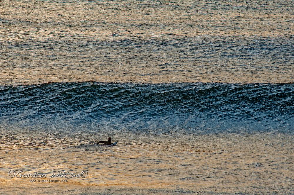 a surfer paddles toward a wave at Montara State Beach on the California Coast